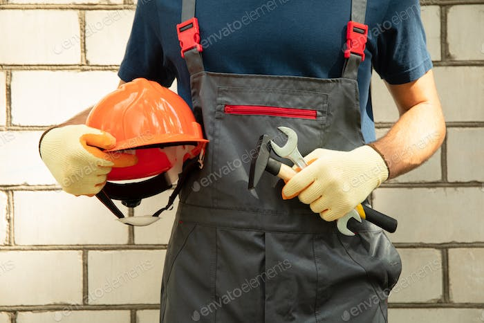 Man in overalls holds safety helmet and construction tools outdoor