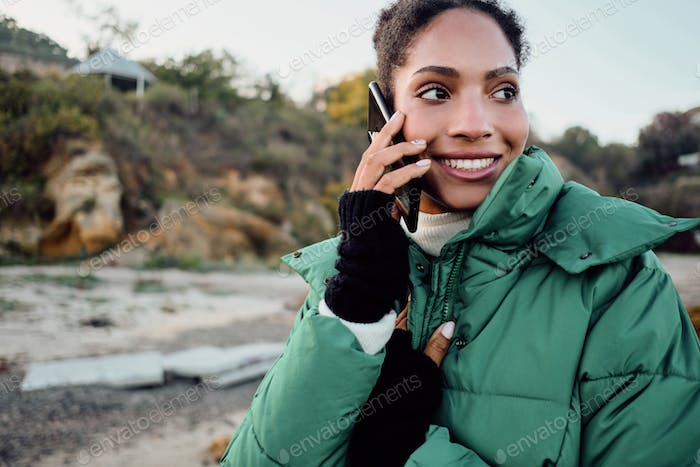 Cheerful African American girl in down jacket happily talking on cellphone by the sea