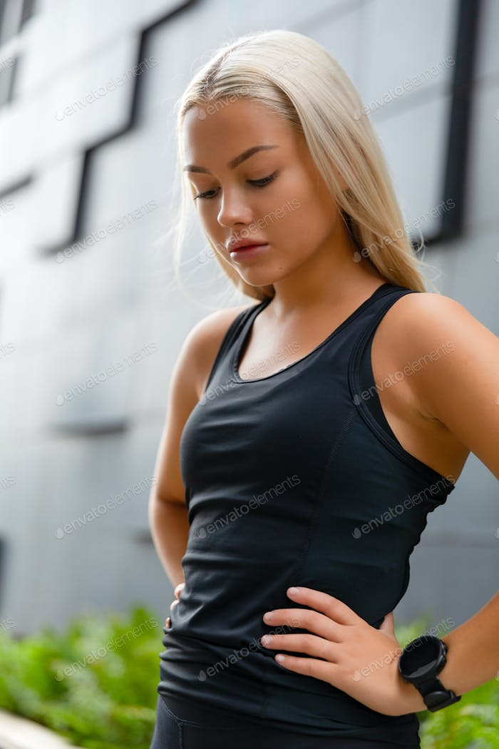 Close-up of fit woman rests with hands on her hips in city