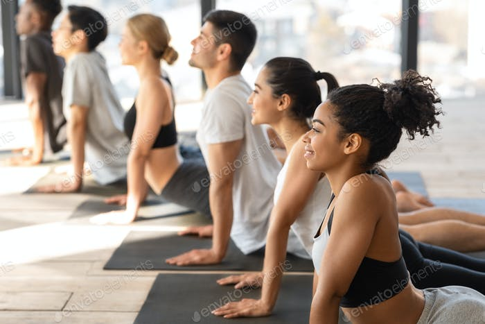 Diverse Multiethnic Men And Women Practicing Cobra Pose During Group Yoga Lesson