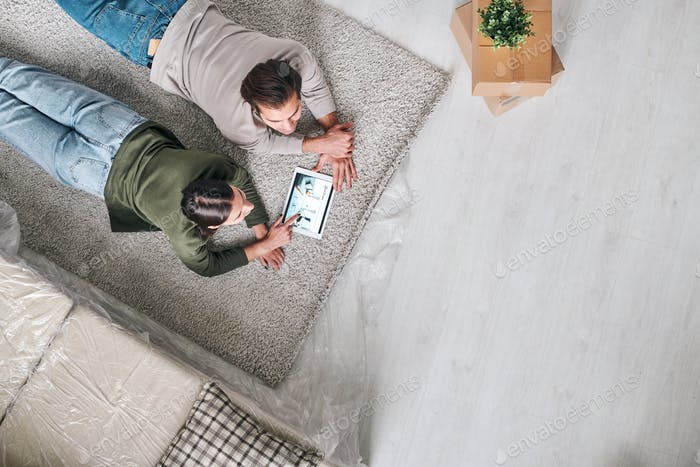 Young restful couple lying on carpet and scrolling through online adverts