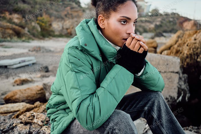 Beautiful stylish African American girl in down jacket warming hands sitting on stones outdoor