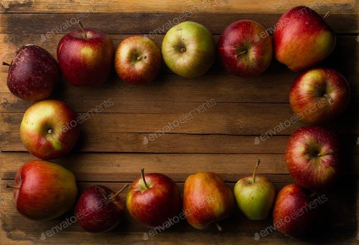 Organic small garden ripe apples on wooden plank
