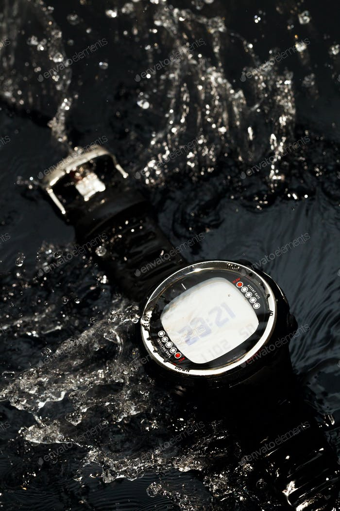 Watch computer for diving in water streams on a black background