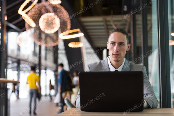 Businessman Using Laptop Computer Outdoors In Restaurant