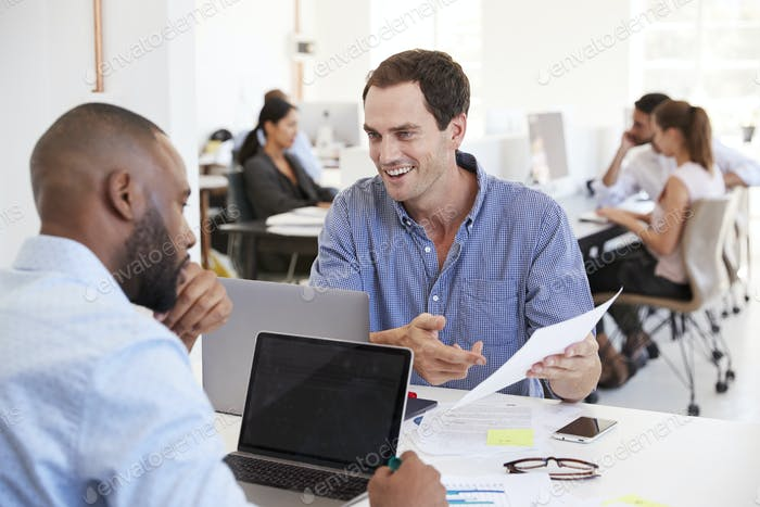 Two men discussing business documents in a busy office