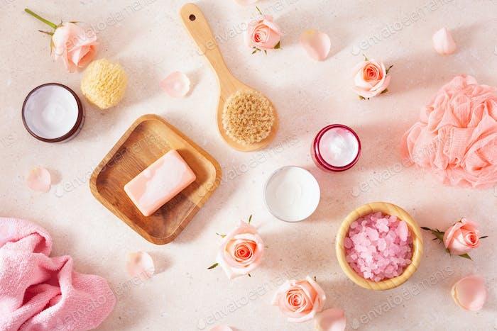Hautpflegeprodukte und Rosenblüten. Naturkosmetik für Heim-Spa-Behandlung
