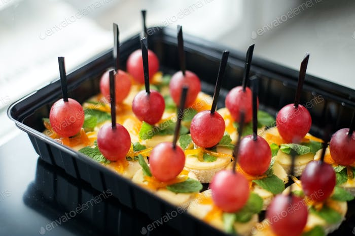 Lots of snacks from toast bread, cheese and grapes in lunch box. Concept for food, snacks, menu