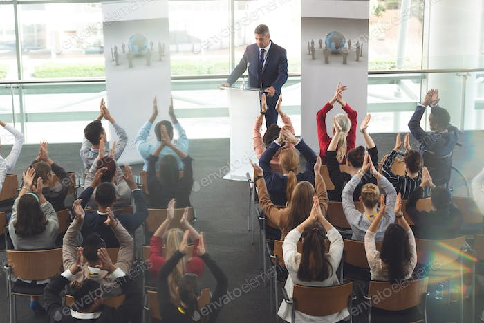 Diverse business people applauding while they are sitting in front businessman at business seminar