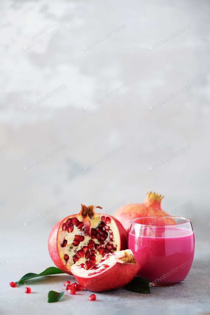 Glass of pomegranate juice with ripe pomegranate fruit on grey concrete background. Banner with copy