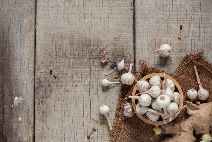 garlic in bowls and ginger on wooden