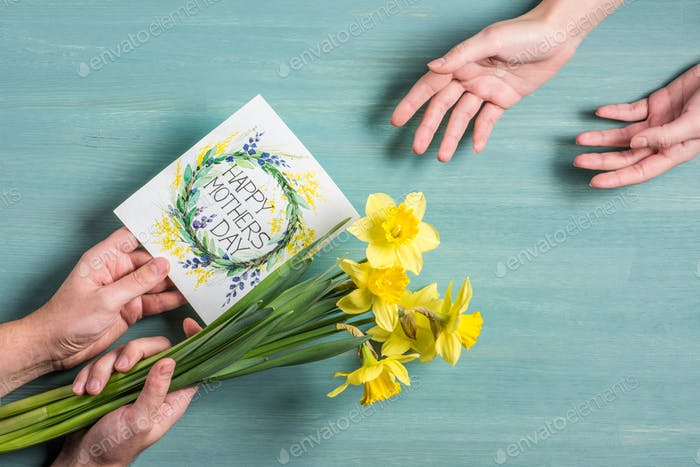 Partial view of man presenting greeting card and daffodils to woman at mothers day