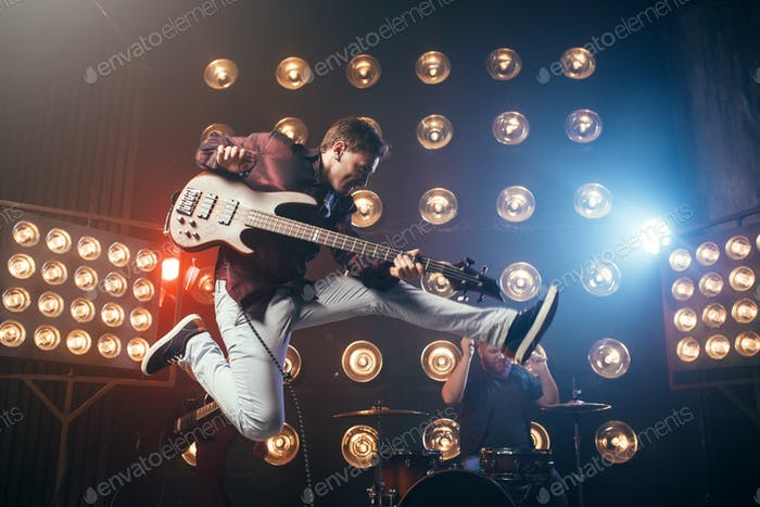 Guitarist plays on bas-guitar, snapshot in a jump