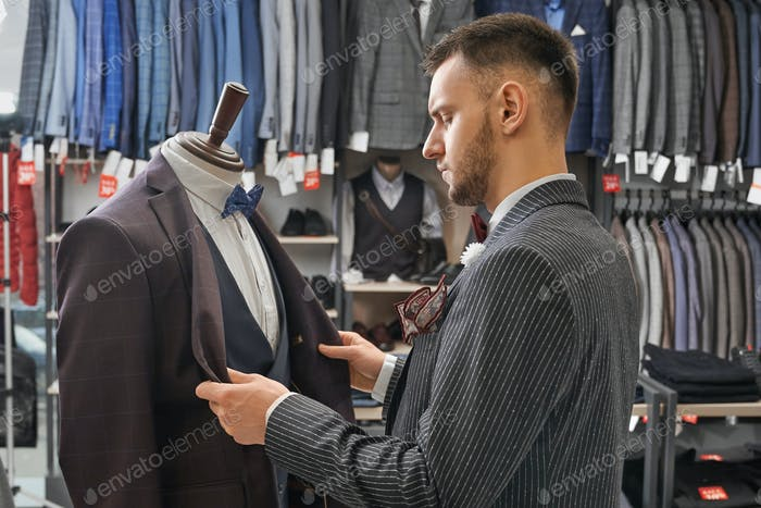 Man choosing clothing on mannequin in boutique