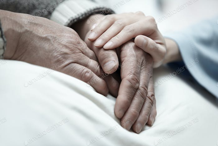 Hand of woman touching senior man in clinic
