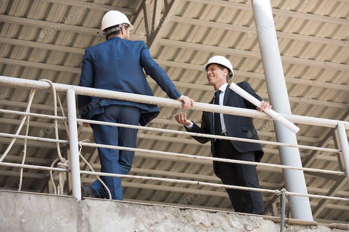 contratistas maduros en ropa formal hablando en el sitio de construcción