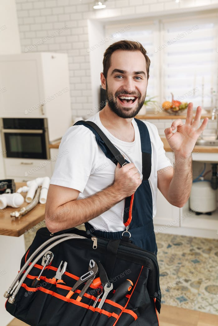 Image of plumber man with equipment gesturing okay sign in apartment