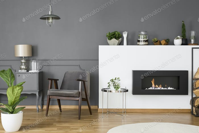 Grey armchair between fireplace and cabinet with lamp in flat in
