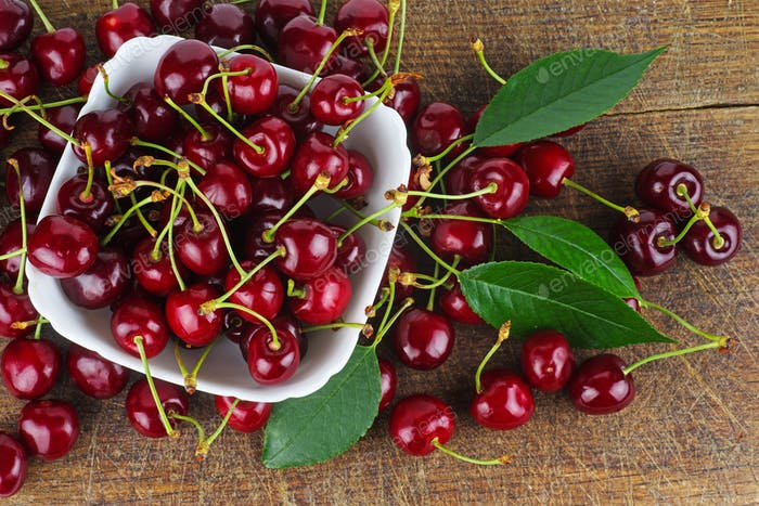 Red cherries in white bowl on wooden background
