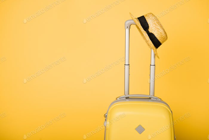 bright yellow travel bag and straw hat on yellow background