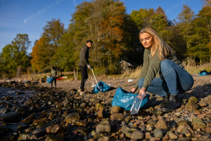 Focused young woman in environment conservation team picking up plastic at beach