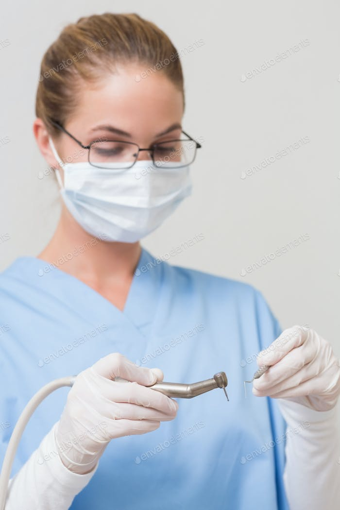 Dentist in blue scrubs holding drill at the dental clinic