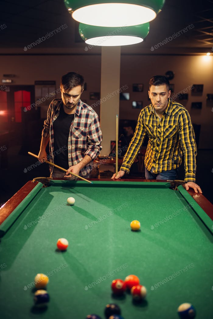 Two male billiard players with cue, poolroom