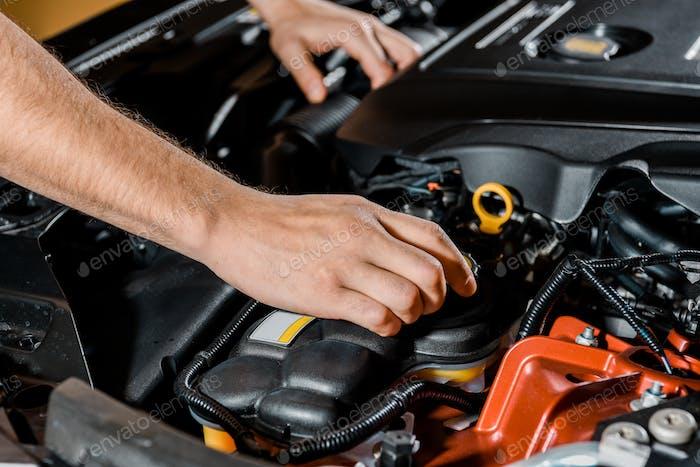 abgeschnittene Aufnahme eines Automechanikers, der das Auto überprüft