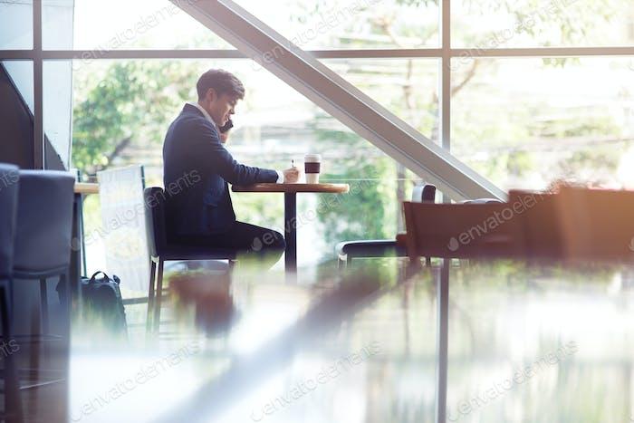Agradable estudiante de secundaria sentado en la cafetería