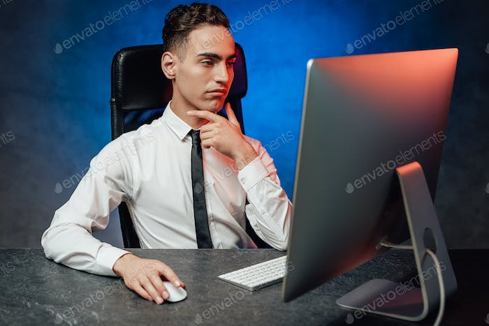 Young businessman is making decision sitting at the office, analyzing the data in the computer
