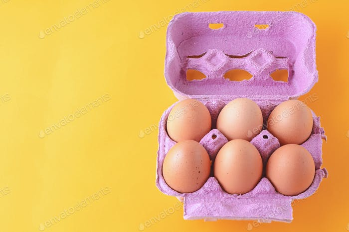 Top view of six brown eggs on box