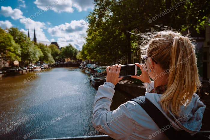 Rear view of female tourist taking photo of canal in Amsterdam on the mobile phone on sunny autumn