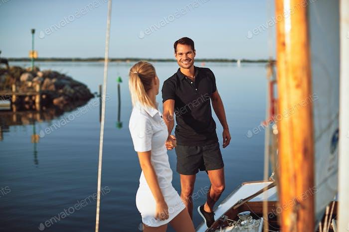 Lächelnd Paar zusammen auf dem Deck ihrer Yacht zu Fuß