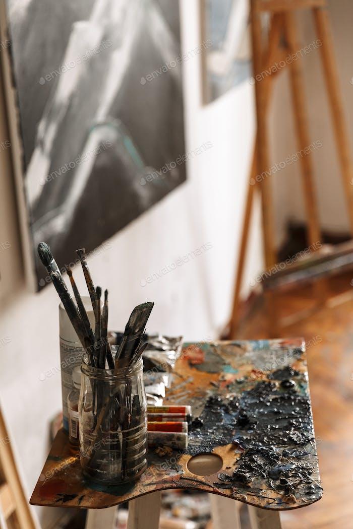 Bild des Künstler-Arbeitsplatzes mit Malwerkzeugen und Kunstwerken an der Wand