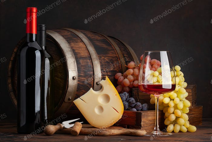 Wine bottles, grapes, cheese and glass of red wine