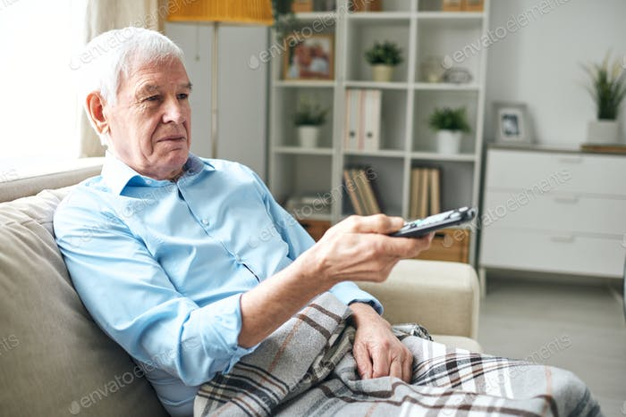 Old man with checkered plaid sitting on couch and using remote control