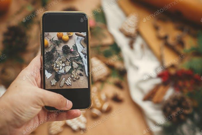 Mano sosteniendo el teléfono y tomando fotos de la composición navideña de galletas festivas de pan de jengibre