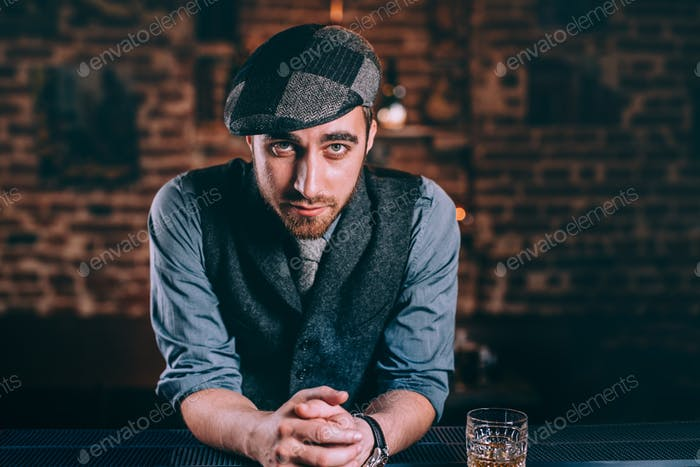 Handsome bartender enjoying a night in bar, having an alcoholic drinks at the counter