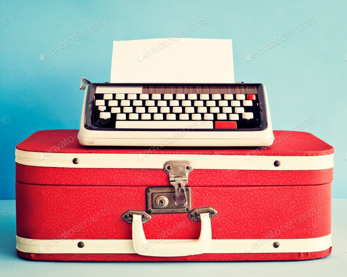Vintage typewriter over antique suitcase