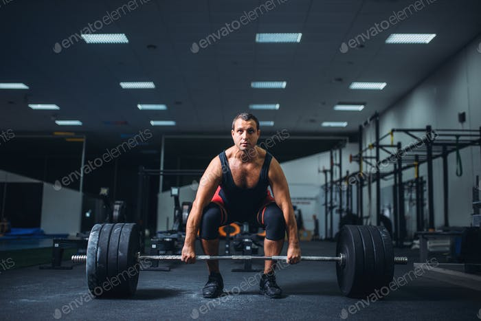 Male powerlifter starting deadlift barbell in gym
