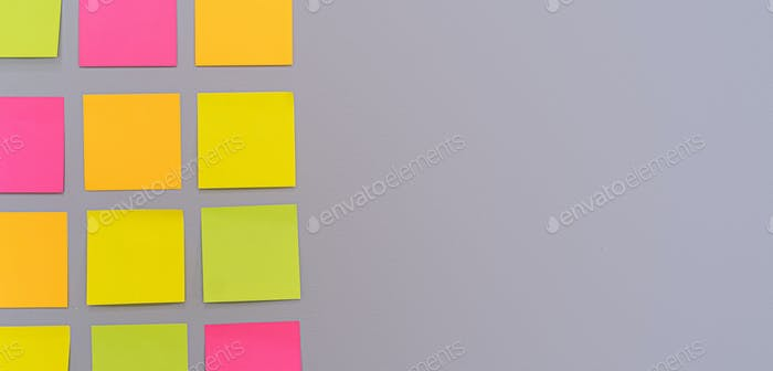 Horizontal photo of table made of multicolored stickers on lilac wall