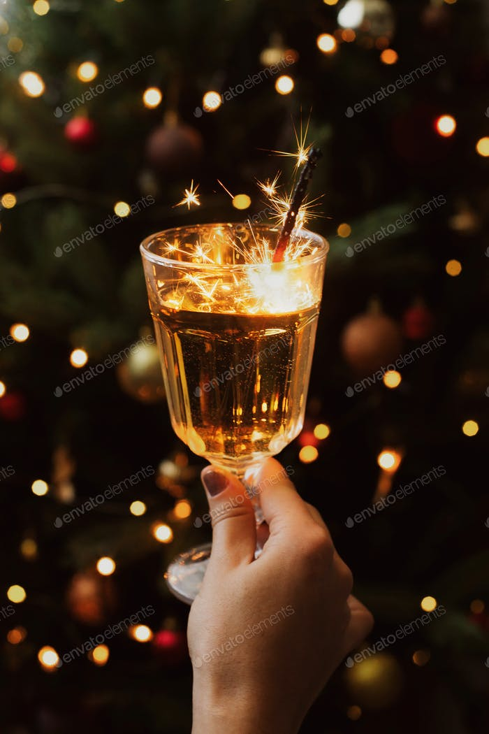 Happy New Year! Burning firework in champagne glass at christmas tree with lights in dark room