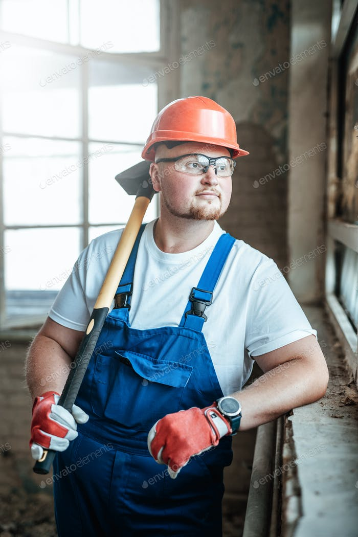 Handsome builder stands by the window and holds a huge hammer