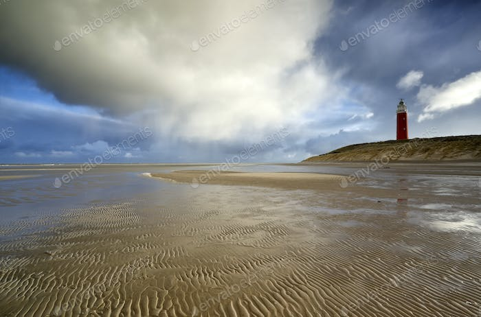 rain clouds over red lighthouse and sea coast