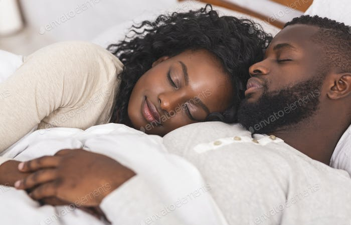 Portrait of black family couple sleeping together in bed