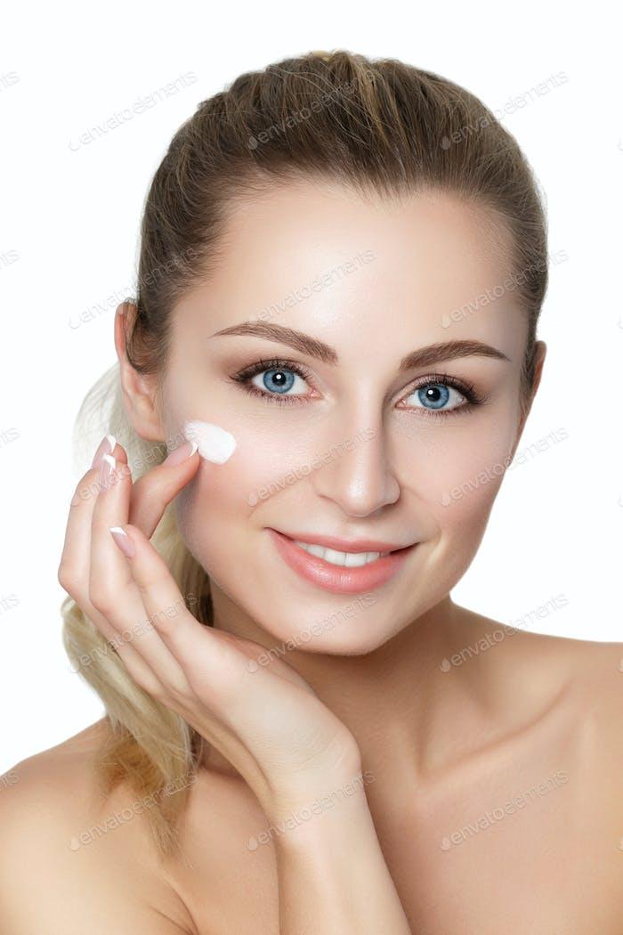 Beautiful young blonde woman applying moisturizing face cream