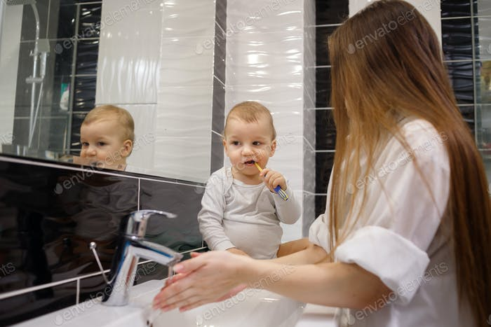 Child brushing teeth sitting on sink near mirror in bathroom. His mother monitoring action