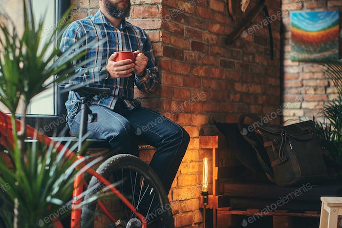 Adult bearded hipster male holds a cup of morning coffee at a studio with a loft interior.