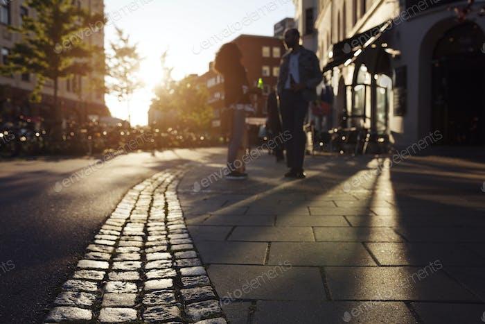 Friends standing on sidewalk and talking