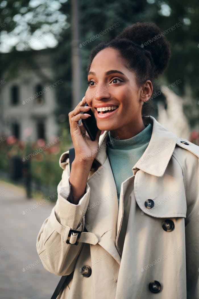 Pretty emotional stylish African American girl in trench coat happily talking on cellphone outdoor